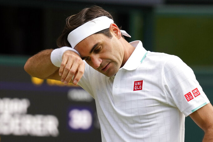 FILE - In this July 7, 2021, file photo, Switzerland's Roger Federer wipes his brow during the men's singles quarterfinals match against Poland's Hubert Hurkacz on day nine of the Wimbledon Tennis Championships in London. Federer pulled out of the upcoming hard-court tournaments in Toronto and Cincinnati on Thursday, Aug. 5, 2021, citing lingering issues with his surgically repaired knee and shedding doubt on his status for the U.S. Open. (AP Photo/Kirsty Wigglesworth, File)