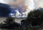 Late afternoon light catches smoke from the Cold Springs Canyon Pearl Hill Fire near a structure that appeared to be empty long before the fire, Monday, Sept. 7, 2020, near Omak, Wash. (Tyler Tjomsland/The Spokesman-Review via AP)