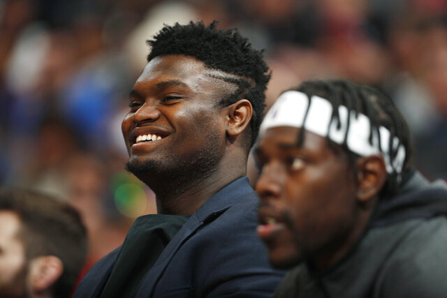Injured New Orleans Pelicans forward Zion Williamson, left, and guard Jrue Holiday watch from the bench during the second half of the team's NBA basketball game against the Denver Nuggets on Wednesday, Dec. 25, 2019, in Denver. The Pelicans won 112-100. (AP Photo/David Zalubowski)