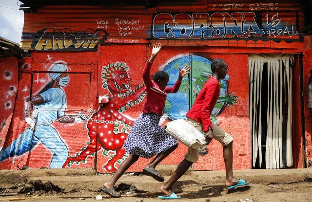 Children run down a street past an informational mural warning people about the dangers of the COVID-19 coronavirus, in the Kibera slum of Nairobi, Kenya on Wednesday, June 3, 2020. (AP Photo/Brian Inganga)