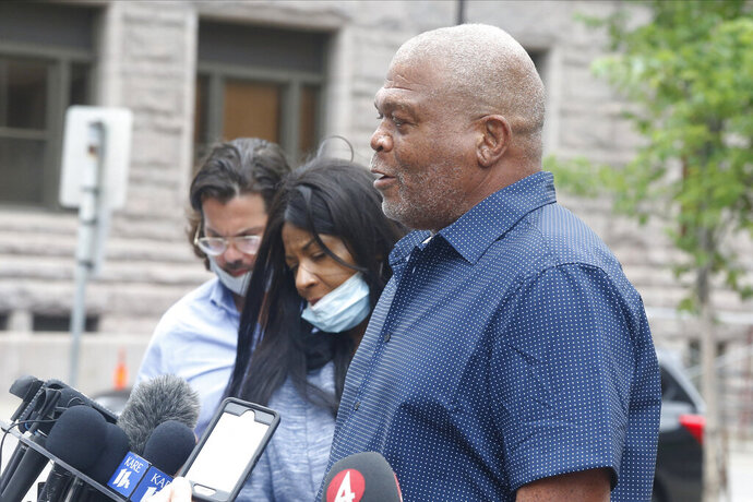 FILE - In this June, 29, 2020 file photo, George Floyd's uncle, Selwyn Jones, right, and his aunt, Angela Harrelson, center, address the media in Minneapolis. Local residents say a South Dakota police department has removed a decal from its squad cars that featured a Confederate battle flag next to an American flag. Dave Mogard, the police chief in Gettysburg, declined to confirm that the decal had been removed, saying Thursday, July 2, 2020, that the City Council would discuss the issue at a meeting next week. Several locals, including Selwyn Jones, an uncle of George Floyd, say the decal had been removed from the department's squad cars and station doors. (AP Photo/Jim Mone File)