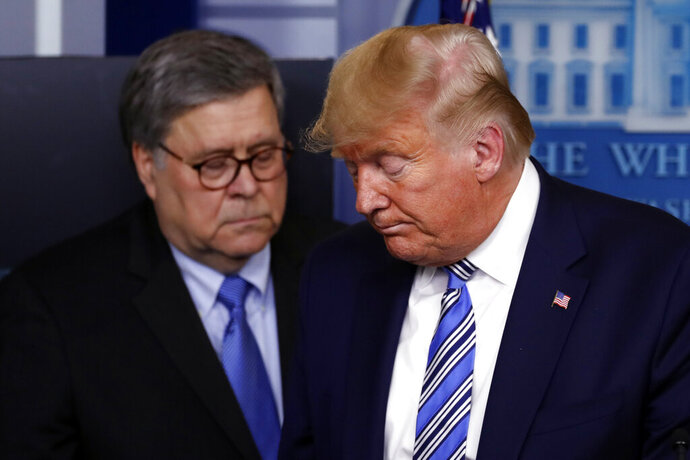 FILE - In this March 23, 2020, file photo President Donald Trump moves from the podium to allow Attorney General William Barr to speak about the coronavirus in the James Brady Briefing Room in Washington. The relationship between President Donald Trump and top ally Attorney General William Barr is fraying over the lack of splashy indictments so far in the Justice Department's investigation into the origins of the Russia probe, according to people familiar with the matter. (AP Photo/Alex Brandon, File)