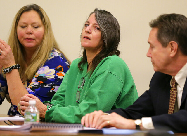 FILE - In a Thursday, Jan. 5, 2017 file photo, Michelle Lodzinski, sits with Chris Davitt, left, and her defense attorney Gerald Krovatin during her sentencing hearing, where she was sentenced to 30 years for the 1991 murder of her 5 year-old son Timothy Wiltsey, at Middlesex County Court in New Brunswick, N.J. One of New Jersey's most infamous cold cases entered another chapter Tuesday, Oct. 27, 2020, when the state's Supreme Court heard arguments on whether the Florida woman's 2016 conviction for killing her 5-year-old son 25 years earlier should be thrown out. (Tanya Breen/The Asbury Park Press via AP, Pool, File)