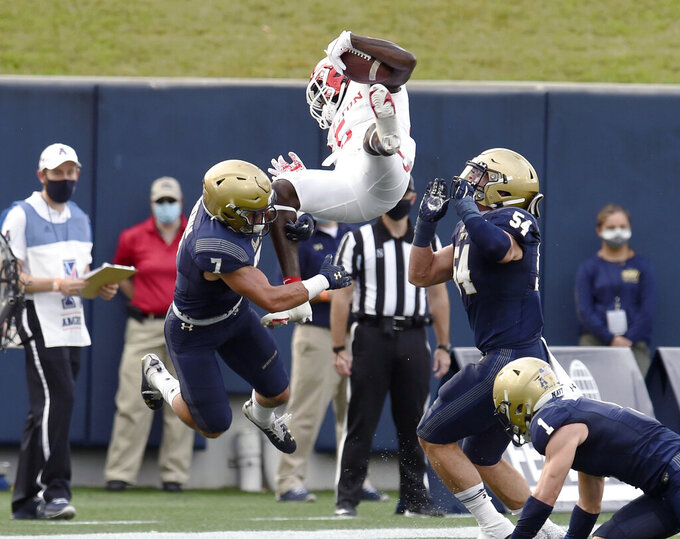 Navy's Kevin Brennan, left, stops Houston's Marquez Stevenson, top, after a catch in the first quarter of an NCAA college football game in Annapolis, Md., Saturday, Oct. 24, 2020. (Paul W. Gillespie/The Baltimore Sun via AP)