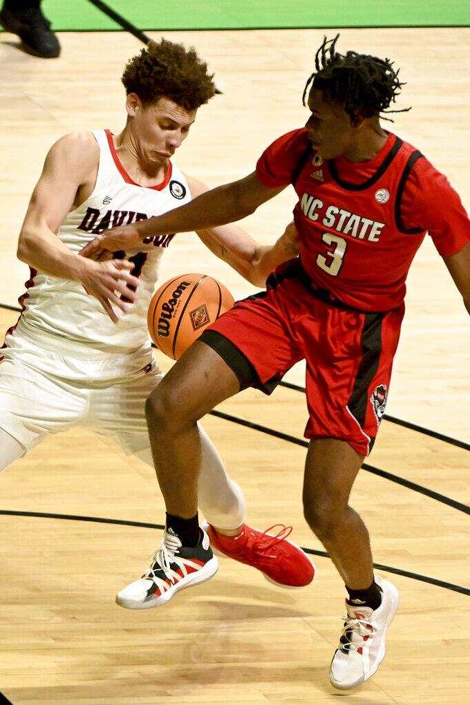 North Carolina State guard Cam Hayes (3) and Davidson guard Kellan Grady (31) go after a loose ball in the first half of an NCAA college basketball game in the first round of the NIT, Thursday, March 18, 2021, in Denton, Texas. (AP Photo/Matt Strasen)