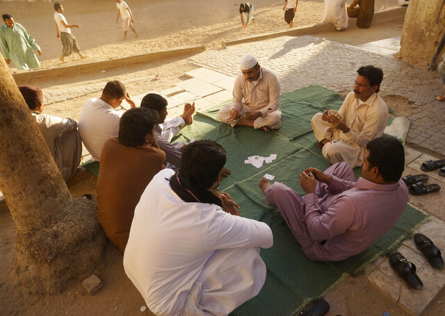 FILE - In this Jan. 24, 2020 file photo, workers play cards during their holiday in the Old City of Jiddah, Saudi Arabia.  On Wednesday, Nov. 4, 2020, Saudi Arabia, announced reforms that will abolish some key restrictions tying millions of low-paid and vulnerable migrant workers to their employers in conditions that have been rife with abuse and exploitation. (AP Photo/Amr Nabil, File)