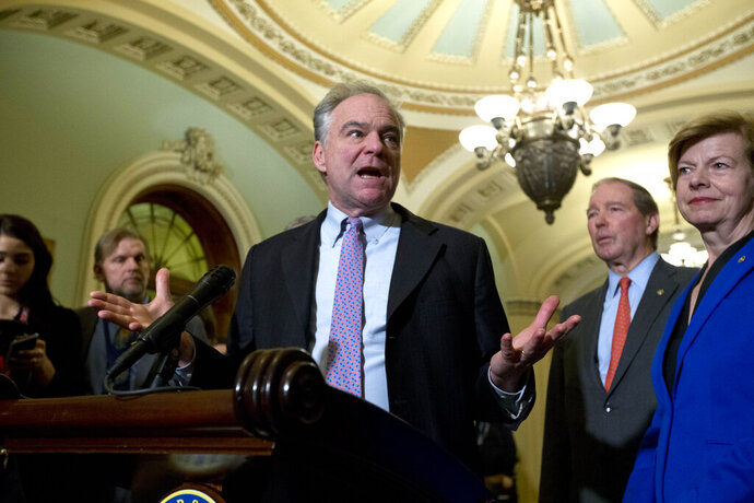 Sen. Tim Kaine D-Va., accompanied by Sen. Tammy Baldwin, D-Wis., and other senators, speaks during a news conference outside of the Senate chamber, on Capitol Hill in Washington, Tuesday, Jan. 14, 2020. (AP Photo/Jose Luis Magana)