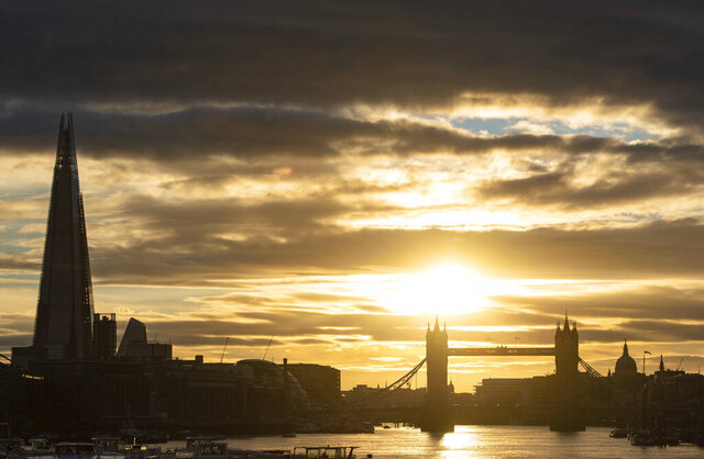 The sun sets behind the London skyline, including from left, the Shard, Tower Bridge and the dome of St Paul's Cathedral as the warm weather continues, in London, Wednesday, Aug. 5, 2020. (Dominic Lipinski/PA via AP)