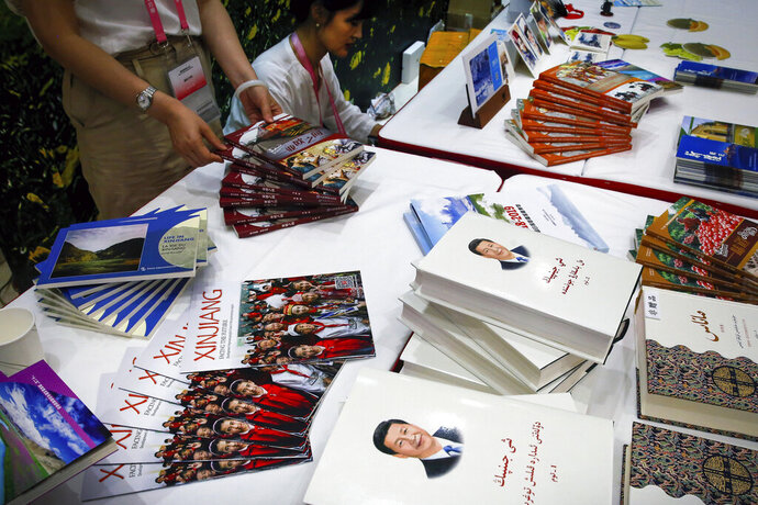 FILE - In this July 30, 2019, file photo, copies of the book on the governance of Chinese President Xi Jinping are displayed with booklets promoting Xinjiang during a news conference by Shohrat Zakir, chairman of China's Xinjiang Uighur Autonomous Region, at the State Council Information Office in Beijing. The Trump administration is slapping travel bans on Chinese officials involved in a massive crackdown against Uighurs and other Muslim minorities in its west. The State Department says it won't issue visas to Chinese government and communist party officials believed to be responsible for or complicit in mass detentions and abuses in western Xinjiang province. (AP Photo/Andy Wong, File)