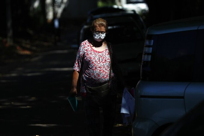 Lina Barrios walks outside the ICU of the Respiratory Hospital INERAM where her son is being treated for COVID-19 in Asuncion, Paraguay, Wednesday, March 3, 2021. Barrios said she has had to buy her son's medication at pharmacies because the hospital is out, costing her $8,400 in two weeks. (AP Photo/Jorge Saenz)