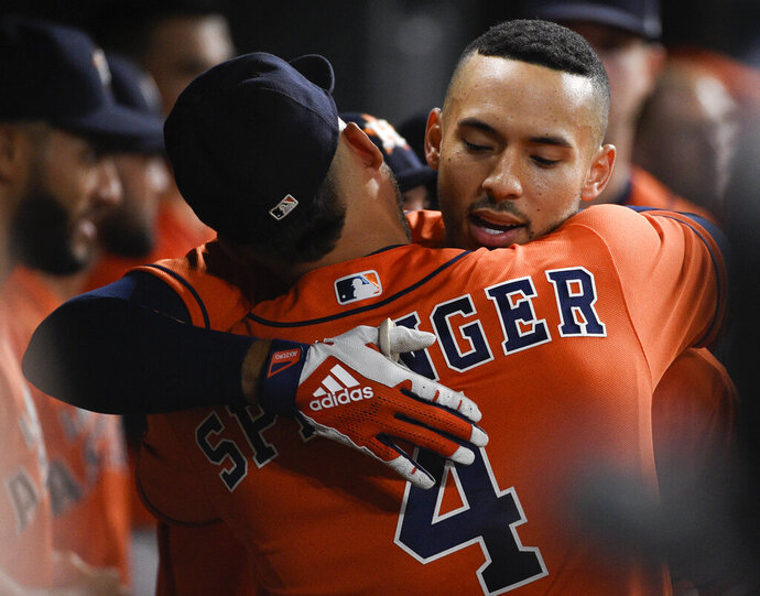 Houston Astros' Carlos Correa, right, hugs George Springer after hitting a solo home run off Los Angeles Angels starting pitcher Jaime Barria during the third inning of a baseball game Friday, Sept. 20, 2019, in Houston. (AP Photo/Eric Christian Smith)