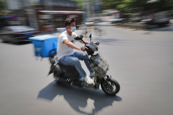 A food delivery worker wearing a protective face mask to help curb the spread of the new coronavirus rides on a street in Beijing, Sunday, June 21, 2020. According to state media reports, nearly one hundred thousand delivery workers have to accept the nucleic acid testing, a countermeasure to prevent the spread of the virus in the capital city. (AP Photo/Andy Wong)
