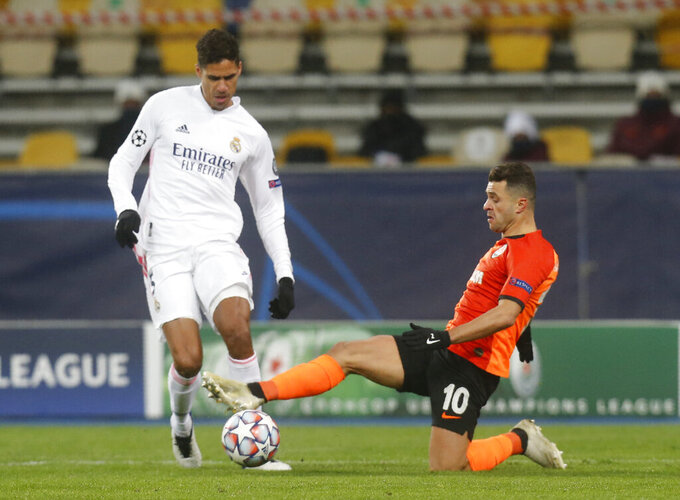 Real Madrid's Raphael Varane, left, and Shakhtar's Junior Moraes challenge for the ball during the Champions League, Group B, soccer match between Shakhtar Donetsk and Real Madrid at the Olimpiyskiy Stadium in Kyiv, Ukraine, Tuesday, Dec. 1, 2020. (AP Photo/Efrem Lukatsky)