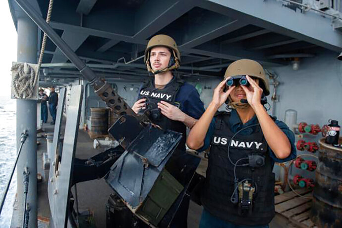 In this Tuesday, Nov. 19, 2019, photo made available by U.S. Navy, Master-At-Arms Seaman Khang Ho, right, and Seaman Shane Mitchell stand guard on the aircraft carrier USS Abraham Lincoln as it transits the Strait of Hormuz. The U.S. aircraft carrier Abraham Lincoln sent to the Mideast in May over tensions with Iran transited the narrow Strait of Hormuz for the first time on Tuesday. The ship previously had been in the Arabian Sea outside of the Persian Gulf. (Mass Communication Specialist 3rd Class Zachary Pearson/U.S. Navy via AP)