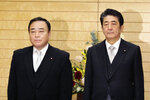 Japan's new Trade Minister Hiroshi Kajiyama, left, poses with Prime Minister Shinzo Abe for a photo at Abe's official residence in Tokyo Friday, Oct. 25, 2019. Kajiyama replaced Isshu Sugawara who resigned Friday a month into his job in a scandal over condolence money, expensive melons and other gifts allegedly offered to election supporters. Abe was quick to remove a potential damage to his Cabinet.(Toshiyuki Matsumoto/Kyodo News via AP)