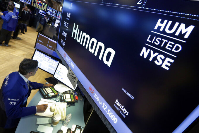 FILE - In this June 8, 2015, file photo specialist Anthony Rinaldi works adjacent to the post that handles Humana, on the floor of the New York Stock Exchange.  Humana is spending $5.7 billion to jump deeper into delivering care at home, a trend that took off during the pandemic and one the health insurer expects will continue to grow. The insurer said Tuesday, April 27, 2021,  that it will buy the rest of Kindred at Home after initially acquiring a 40% stake in the care provider a few years ago.  (AP Photo/Richard Drew, File)