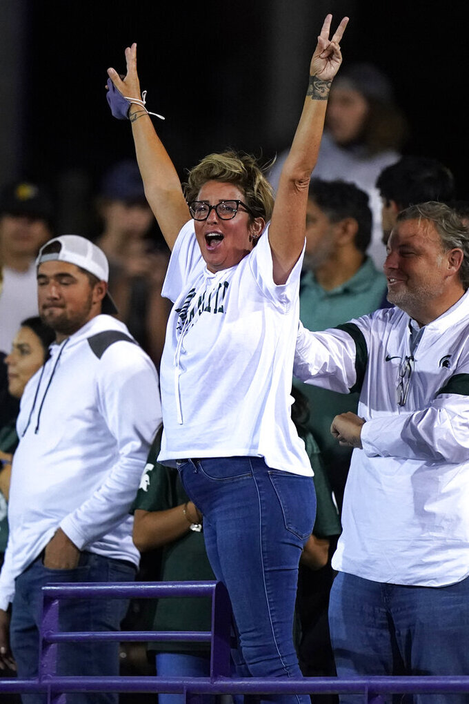 A Michigan State fan cheers for team before an NCAA college football game against Northwestern in Evanston, Ill., Friday, Sept. 3, 2021. (AP Photo/Nam Y. Huh)