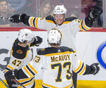 Boston Bruins centre Colby Cave (26) celebrates with teammates Torey Krug (47) and Charlie McAvoy (73) after scoring the second goal during second period NHL hockey action against the Montreal Canadiens, in Montreal, Monday, Dec. 17, 2018. (Ryan Remiorz/The Canadian Press via AP)