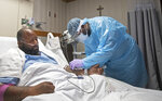 A nurse treats COVID-19 patient Cedric Daniels, 37, of Gonzales, La., at Our Lady of the Lake Regional Medical Center in Baton Rouge, Monday, Aug. 2, 2021. Louisiana is leading the nation in the number of new COVID cases per capita and remains one of the bottom five states in administering vaccinations.   (AP Photo/Ted Jackson)