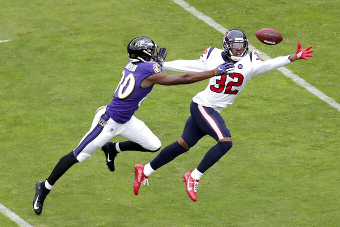 Houston Texans cornerback Lonnie Johnson (32) and Baltimore Ravens wide receiver Miles Boykin (80) reach for a ball thrown by Ravens quarterback Lamar Jackson, not visible, during the first half of an NFL football game, Sunday, Nov. 17, 2019, in Baltimore. (AP Photo/Julio Cortez)