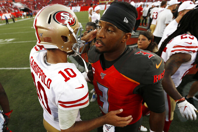 Tampa Bay Buccaneers quarterback Jameis Winston, right, embraces San Francisco 49ers quarterback Jimmy Garoppolo after the second half an NFL football game, Sunday, Sept. 8, 2019, in Tampa, Fla. The San Francisco 49ers won 31-17. (AP Photo/Mark LoMoglio)