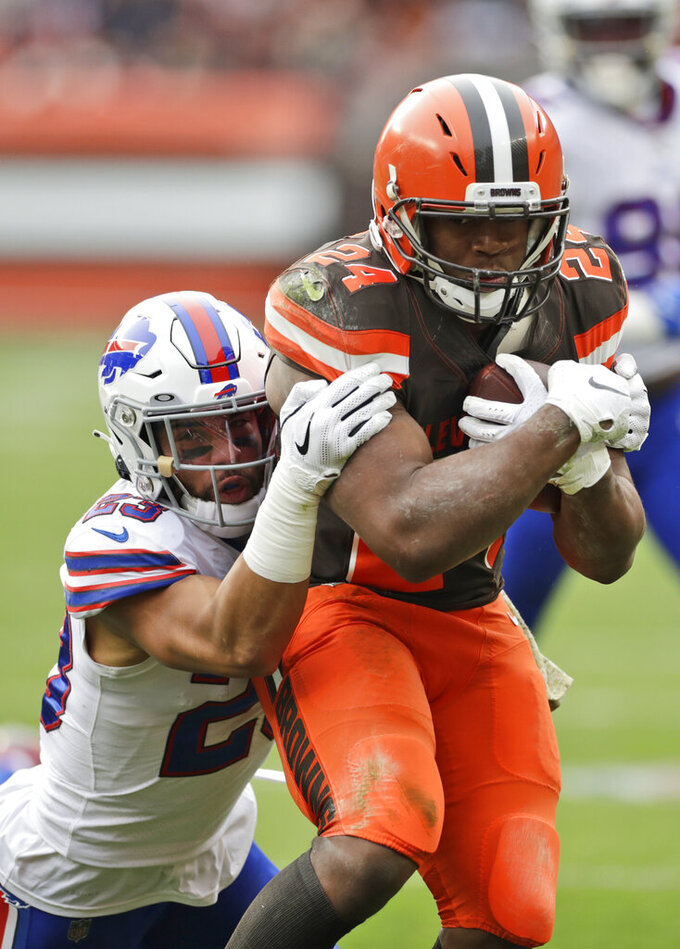 Cleveland Browns running back Nick Chubb (24) is tackled by Buffalo Bills strong safety Micah Hyde (23) during the first half of an NFL football game, Sunday, Nov. 10, 2019, in Cleveland. (AP Photo/Ron Schwane)