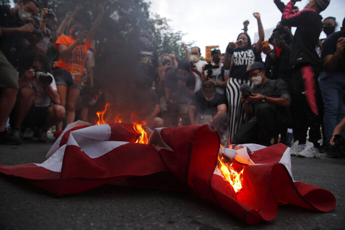 Protesters and journalists gather around a United States flag as it burns outside the White House on a section of 16th Street that has been renamed Black Lives Matter Plaza, Saturday, July 4, 2020, in Washington. (AP Photo/Maya Alleruzzo)