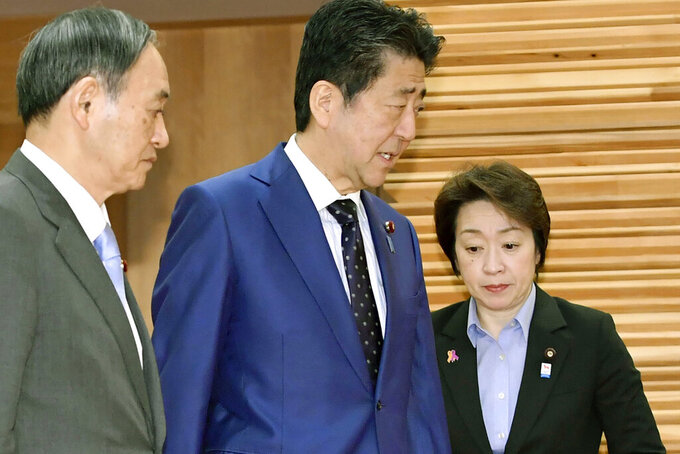 Japanese Prime Minister Shinzo Abe, center, walks past Olympic Minister Seiko Hashimoto, right, to attend a cabinet meeting at his official residence in Tokyo Tuesday, March 24, 2020. Hashimoto said the global pandemic of coronavirus infections should end before Japan can proceed with hosting the Tokyo Olympic Games, after the meeting. Tokyo's organizers and International Olympic Committee are discussing a possible postponement and other scenarios. Abe and IOC President Thomas Bach are expected to hold telephone talks later Tuesday. At left is Chief Cabinet Secretary Yoshihide Suga. (Yoshitaka Sugawara/Kyodo News via AP)