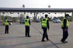 Security personnel wearing face masks to protect against the spread of new coronavirus direct vehicles entering Wuhan city at a toll gate in Wuhan in central China's Hubei Province, Wednesday, April 8, 2020. After 11 weeks of lockdown, the first train departed Wednesday morning from a re-opened Wuhan, the origin point for the coronavirus pandemic, as residents once again were allowed to travel in and out of the sprawling central Chinese city. (AP Photo/Ng Han Guan)