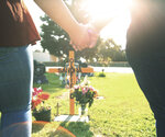 Lori Gonzalez, right and her daughter, Mariah Rodriguez, hold hands at the temporary grave marker of her sister and Kaiser Permanente Fresno Medical Center nurse, Sandra Oldfield, at the Sanger Cemetery in Sanger, Calif., Saturday, Aug. 29, 2020. Oldfield became ill and then died after being exposed to a patient who had COVID-19. Workers at the hospital said they did not have the proper personal protective equipment. (AP Photo/Gary Kazanjian)