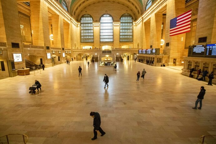 People make their way inside Grand Central Terminal, Wednesday, March 25, 2020, in New York. Hospitalizations from COVID-19 were rising faster than expected in New York as residents and leaders prepared for a peak in cases that is expected to still be weeks away. Temporary hospitals, and even a morgue in Manhattan, are being setup. (AP Photo/Mary Altaffer)