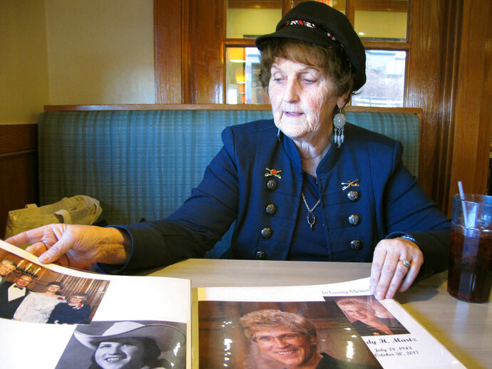 In this Wednesday, Oct. 3, 2018 photo, Lewis and Clark Republican Women President Shirley Herrin looks at photographs of former Montana Gov. Judy Martz in Helena, Mont. Herrin and Democratic party leaders say women are highly motivated to vote in this year's election. (AP Photo/Matt Volz)