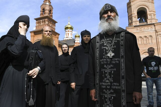 FILE In this file photo taken on Wednesday, June 17, 2020, Father Sergiy, a Russian monk who has defied the Russian Orthodox Church's leadership, right, speaks to journalists in Russian Ural's Sredneuralsk, Russia. The Russian Orthodox Church on Friday July 3, 2020, defrocked Father Sergiy, who has defied the coronavirus lockdown orders and has taken control over a monastery. (AP Photo/Vladimir Podoksyonov, FILE)