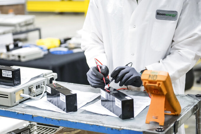 FILE - In this March 28, 2020, file photo, David Yee, an NPI mechanical engineer, tests voltage of new batteries at Bloom Energy in Sunnyvale, Calif. The COVID-19 outbreak has prompted companies large and small to rethink how they do business. Bloom Energy makes hydrogen fuel cells. But recently, they have been refurbishing old ventilators so hospitals can use them to keep coronavirus patients alive. (Beth LaBerge/KQED via AP, Pool, File)