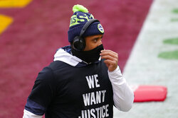 Seattle Seahawks quarterback Russell Wilson adjusting his facemask before the start of an NFL football game against the Washington Football Team, Sunday, Dec. 20, 2020, in Landover, Md. (AP Photo/Andrew Harnik)