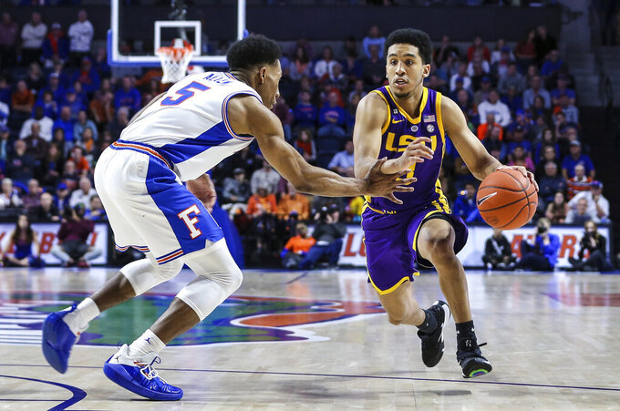 FILE - In this Wednesday, March 6, 2019 file photo, LSU guard Tremont Waters (3) advances the ball defended by Florida guard KeVaughn Allen (5) during the second half of an NCAA college basketball game in Gainesville, Fla. Tennessee forward Grant Williams is the Associated Press' Southeastern Conference player of the year and Mississippi's Kermit Davis is coach of the year. Williams earned unanimous first-team all-SEC honors for a second straight season. The 14-member media panel also voted Arkansas' Daniel Gafford, Kentucky's PJ Washington, LSU's Tremont Waters and Mississippi State's Quinndary Weatherspoon to the first team. (AP Photo/Gary McCullough, File)
