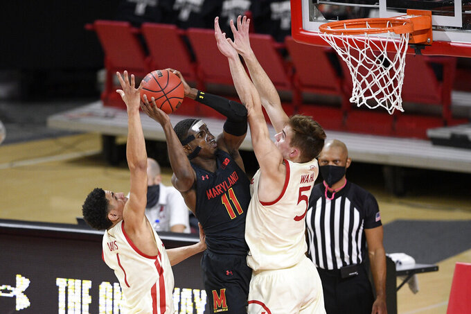 Maryland guard Darryl Morsell (11) goes to the basket between Wisconsin guard Jonathan Davis (1) and forward Tyler Wahl (5) during the first half of an NCAA college basketball game, Wednesday, Jan. 27, 2021, in College Park, Md. Morsell was fouled on the play. (AP Photo/Nick Wass)