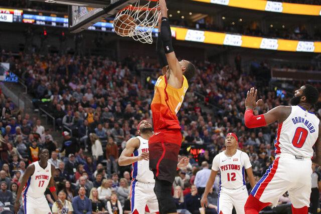 Utah Jazz center Rudy Gobert (27) dunks the basketball with Detroit Pistons guard Bruce Brown (6) watching during the third quarter of an NBA basketball game, Monday, Dec. 30, 2019, in Salt Lake City. The Utah Jazz won 104-81. (AP Photo/Chris Nicoll)
