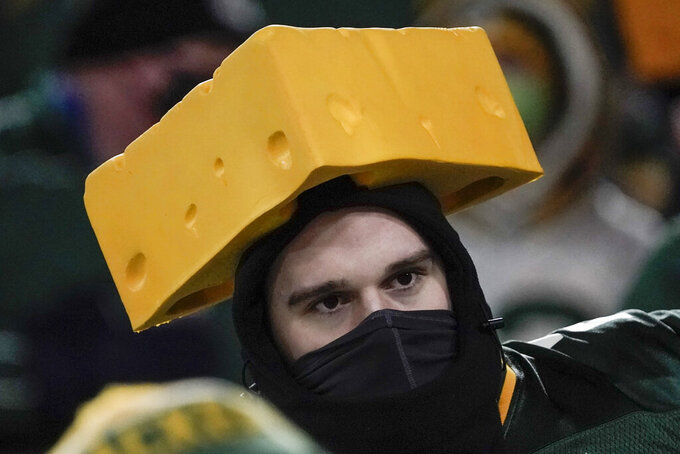 A masked spectator watches the second half of an NFL divisional playoff football game between the Green Bay Packers and the Los Angeles Rams Saturday, Jan. 16, 2021, in Green Bay, Wis. (AP Photo/Morry Gash)