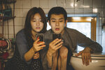 This image released by Neon shows So-dam Park, left, and Woo-sik Choi in a scene from