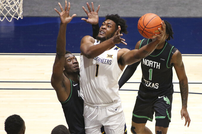 West Virginia forward Derek Culver (1) shoots while defended by North Texas forward Thomas Bell (13) during the first half of an NCAA college basketball game Friday, Dec. 11, 2020, in Morgantown, W.Va. (AP Photo/Kathleen Batten)