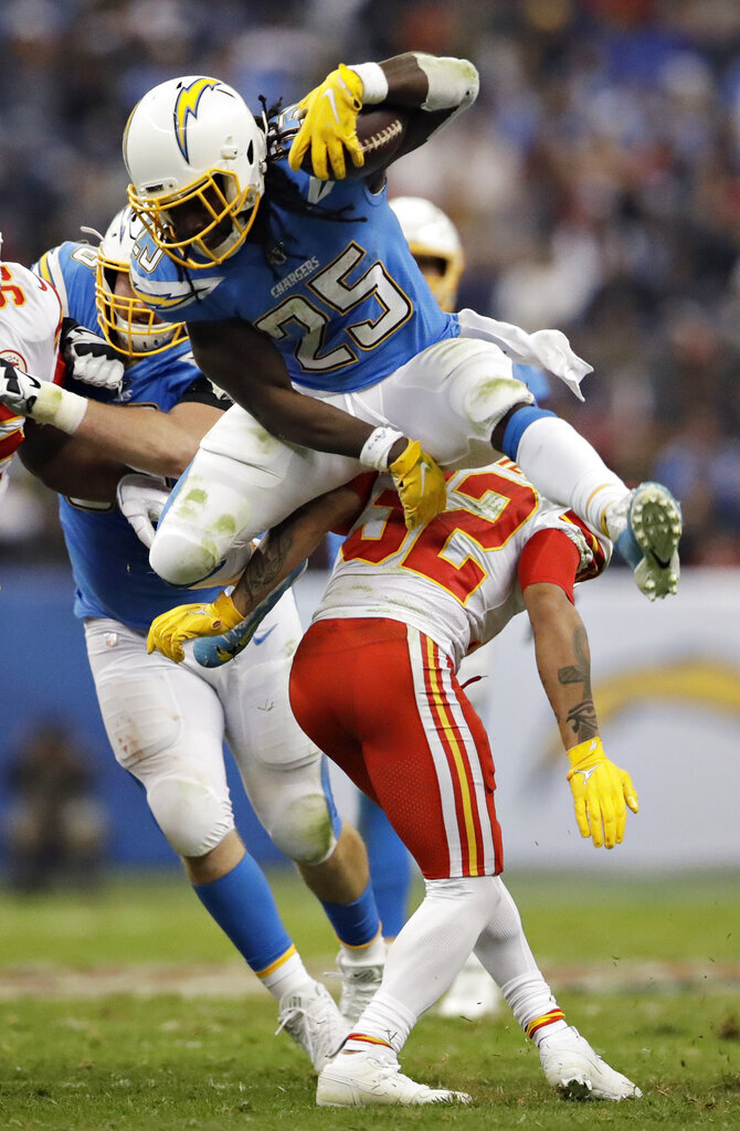 Los Angeles Chargers running back Melvin Gordon, above, leaps over Kansas City Chiefs strong safety Tyrann Mathieu during the first half of an NFL football game Monday, Nov. 18, 2019, in Mexico City. (AP Photo/Marcio Jose Sanchez)