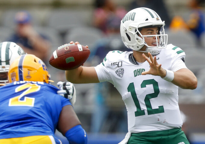 Ohio quarterback Nathan Rourke (12) gets a pass away as Pittsburgh defensive lineman David Green (2) pressures during the first half of an NCAA college football game, Saturday, Sept. 7, 2019, in Pittsburgh. (AP Photo/Keith Srakocic)