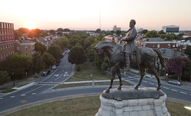 FILE - In this July 31, 2017 file photo, the sun sets behind the statue of confederate General Robert E. Lee on Monument Avenue in Richmond, Va.  Attorneys will be back in court Thursday, July 23, 2020, for a hearing in a lawsuit challenging Virginia Gov. Ralph Northam's plan to remove a giant Confederate statue in Virginia's capital city.(AP Photo/Steve Helber)