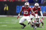 Wisconsin running back Jonathan Taylor (23) runs during the second half of the Big Ten championship NCAA college football game as Ohio State's Cameron Brown (26) watches Saturday, Dec. 7, 2019, in Indianapolis. (AP Photo/Michael Conroy)