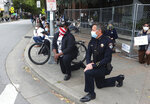 Santa Cruz, Calif., Police Chief Andy Mills, right, and Santa Cruz Mayor Justin Cummings, center, take a knee along with hundreds gathered on Pacific Avenue in downtown Santa Cruz on Saturday May 30, 2020 to honor the memory of George Floyd and bring attention to police violence against black people. Floyd, a handcuffed black man, died in Minneapolis police custody on May 25. (AP Photo/Shmuel Thaler)