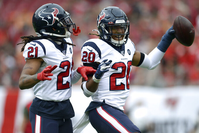 Houston Texans strong safety Justin Reid (20) celebrates with cornerback Bradley Roby (21) after Reid intercepted a pass by Tampa Bay Buccaneers quarterback Jameis Winston during the first half of an NFL football game Saturday, Dec. 21, 2019, in Tampa, Fla. Roby also intercepted a pass by Winston. (AP Photo/Jason Behnken)