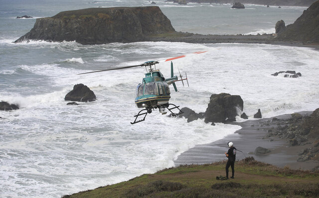 Henry 1, the Sonoma County, Calif., Sheriff's helicopter team, searches Monday, Jan. 4, 2021, for two missing children that were swept away in the surf at Blind Beach, right, that also killed their father Sunday afternoon near Jenner, Calif. A 40-year-old man died after he tried to rescue his two young children who were swept away by a sneaker wave in Sonoma County and are now presumed dead, authorities said. (Kent Porter/The Press Democrat via AP)