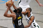 Milwaukee Bucks forward Khris Middleton (22) defends against Brooklyn Nets guard James Harden (13) during the second half of Game 5 of a second-round NBA basketball playoff series Tuesday, June 15, 2021, in New York. (AP Photo/Kathy Willens)