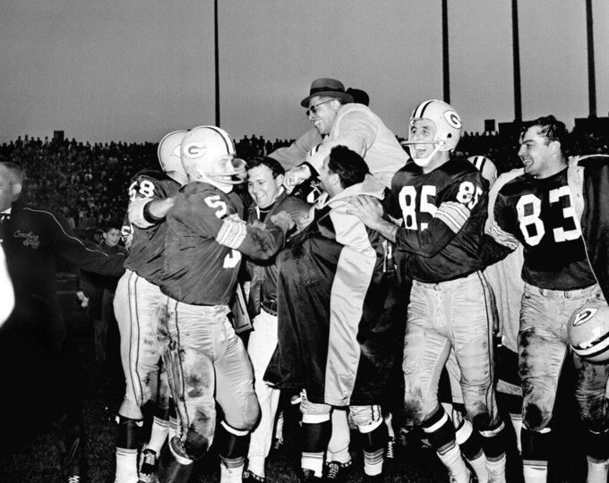 FILE - The Green Bay Packers football team carry coach Vince Lombardi after clinching the NFL West Conference title by beating the New York Giants 20-17 in Milwaukee, Wisc., in this Dec. 3, 1961, file photo. At left is mPaul Hornung (5) and at right is Max McGee (85). The rest of the players are unidentified. The Baltimore Ravens are one victory away from passing Vince Lombardi's Green Bay Packers for the longest preseason winning streak in NFL history. Beating Washington on Saturday would make it 20 in a row. The Packers won 19 in a row from 1959-1962. (AP Photo/DVN)